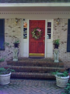 My antiqued red door with shiny brass hardware (Photo Credit: Adroit Ideals)