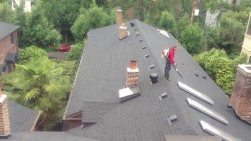 Man on roof using leaf blower